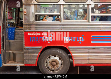 Detail of Thai script on the side of interurban buses parked at Kanchanaburi central bus terminal, in Thailand. The buses are traditionally very colou - Stock Image