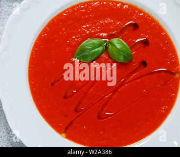 Tomato soup with Basil, spices and olive oil in a white plate close-up. Selective focus - Stock Image