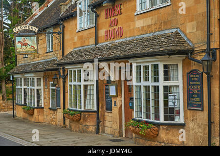Horse and Hound public house in the Cotswold town of Broadway, with an old pub sign advertising Flowers Ales - Stock Image