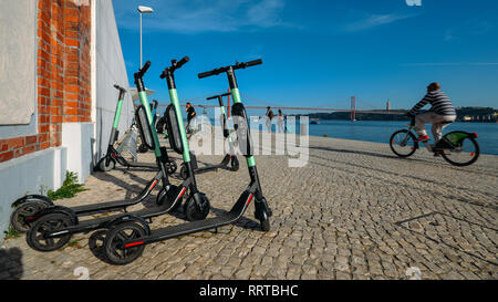 Lisbon, Portugal - Feb 25, 2019: Dockless electric shared scooters parked on the promenade overlooking the Tagus and 25 April Bridge - Stock Image