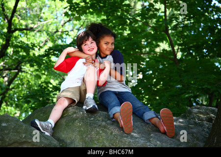 Boy and girl posing on a rock - Stock Image