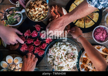 Vertical top view of friends eating together  on a wooden table full of food - friendship and celenration people - concept of friendship with adult me - Stock Image