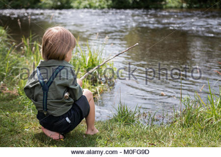 Little boy with old-fashioned fishing rod on a river shore - Stock Image