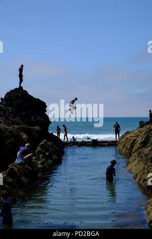 Bude, Cornwall, UK. Holidaymakers jump into the sea from rocks into a natural pool, taking part in a sport known as tombstoning - Stock Image