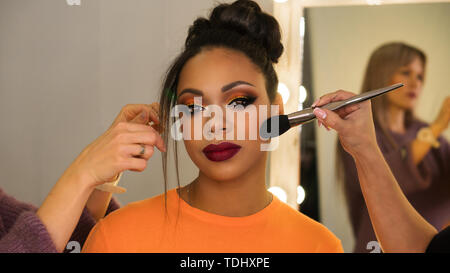 Portrait stylish African American. Girl posing in beauty salon with high hairstyle and make-up party. Work of professional makeup artist and hairstyli - Stock Image