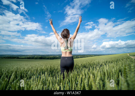 back view of a sportswoman with her arms raised, in a green wheat field. - Stock Image