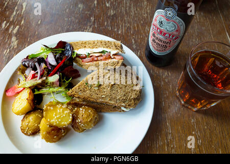 Café lunch a cream cheese and tomato sandwich  on multigrain brown bread with salad sesame potatoes and a glass and bottle of organic Pale Ale - Stock Image