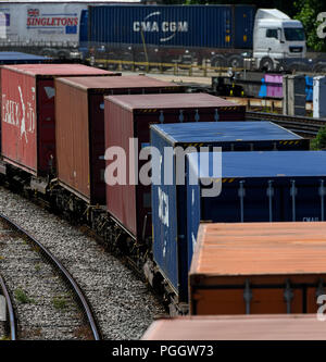 Container railway to Southampton Docks carrying goods for export and import with a lorry carrying containers behind. - Stock Image