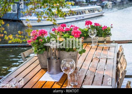 Amsterdam restaurant, tables set for lunch with flowers - Stock Image