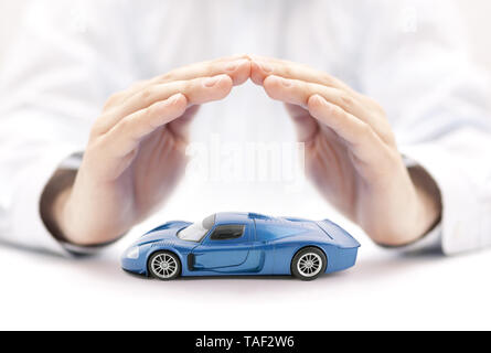 Car insurance concept with blue car toy covered by hands - Stock Image