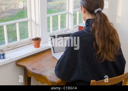 Middle aged woman using Google on her laptop. - Stock Image
