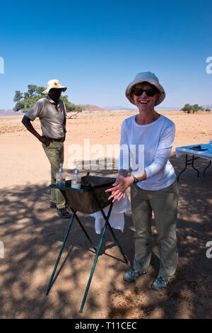 A woman washes before a safari lunch in the Namib-Naukluft Park, Namibia - Stock Image