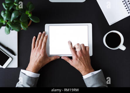 A top view of male hands hodling tablet on a desk. Copy space. - Stock Image