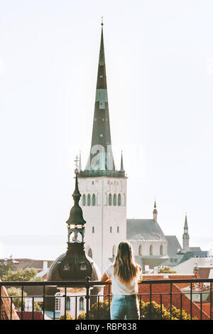 Vacations in Tallinn woman traveling in Estonia touristic viewpoint girl sightseeing St Olav's Church Old Town european historic architecture - Stock Image