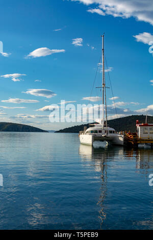 Seascape with cozy sea bay and big white catamaran yacht boat, vacation destination - Stock Image