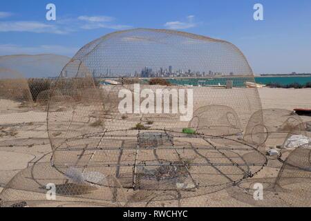Fish traps with Manama behind, Nurana Island, Kingdom of Bahrain - Stock Image