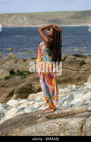 African Woman with Dreadlocks, and Wearing a Colourful Dress, Standing by the Sea. - Stock Image