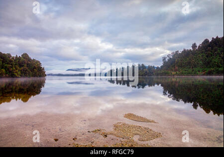 A quiet dawn ay Lake Mapouriki, on the West Coast of New Zealand's South Island. - Stock Image