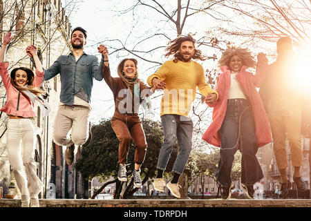 Group of happy friends jumping outdoor - Millennial young people having fun dancing and celebrating at sunset outside - Stock Image