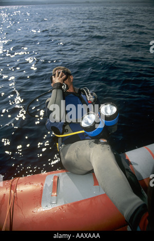 diver doing backward roll off of inflatable dive boat - Stock Image