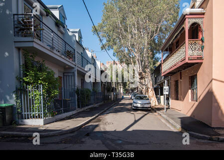 A narrow street lined on both sides with terrace houses, some restored original and some new in Surry Hills, Sydney Australia - Stock Image