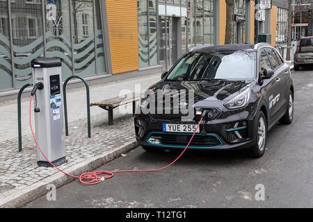 A Kia Niro Plug In Hybrid car attached to an electrical charging station by the side of a road in the town of Trondheim in Norway. - Stock Image