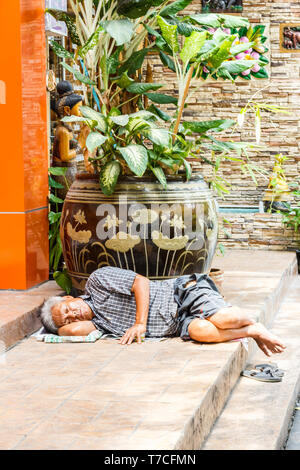 Bangkok, Thailand - 4th August 2017: Old man asleep on some steps. Vagrancy is an ever increasing problem. - Stock Image