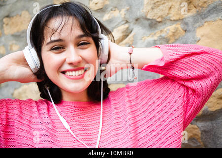 Happy young girl in pink sweater listening to music in white headphones leaning in a street wall. - Stock Image