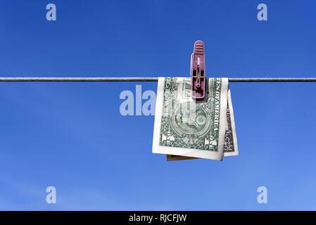 Money laundering of a one US Dollar bill note from the USA on a washing line with blue sky for AML Anti laundering finance business crime ideas - Stock Image