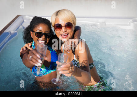 Portrait exuberant young women friends drinking champagne in sunny hot tub - Stock Image