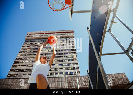 Young female basketball player jumping and throwing the ball to the basket in an urban court - Stock Image