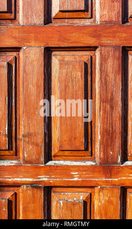 Wooden door showing the texture in the shadow and highlighting the texture - Stock Image