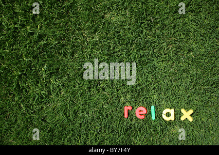 The word 'relax' spelled out in colourful plastic letters, on green grass, taken from a low angle - Stock Image