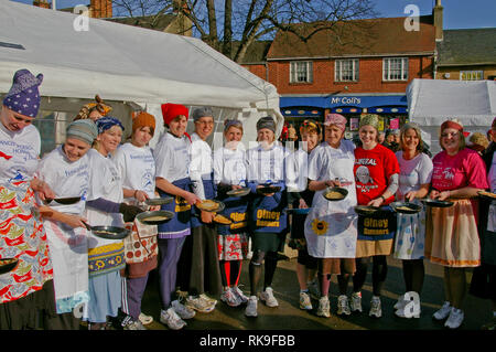 Smiling ladies lining up in the Market Square for the start of famous Olney Pancake Race, said to be the oldest in the world; Buckinghamshire, UK - Stock Image