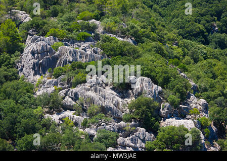 Rock formations with vertical striations surrounded by vegetation on a hillside in Mallorca, Spain. - Stock Image
