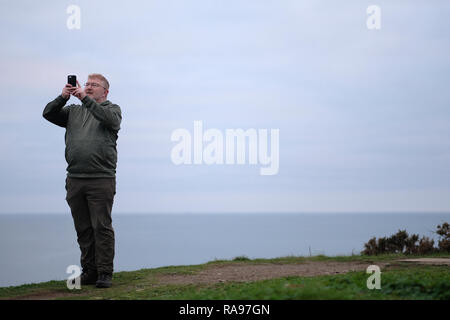 A man on a hill by the sea taking a selfie in Cornwall, UK. - Stock Image