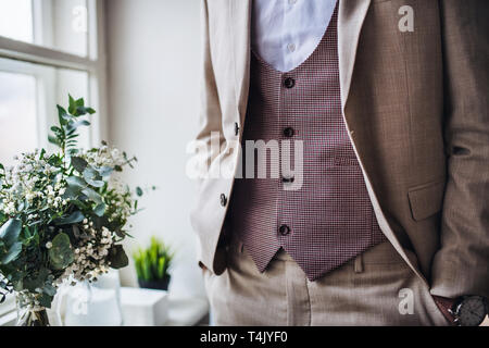 A midsection of man with formal suit standing on an indoor party, hands in pockets. - Stock Image