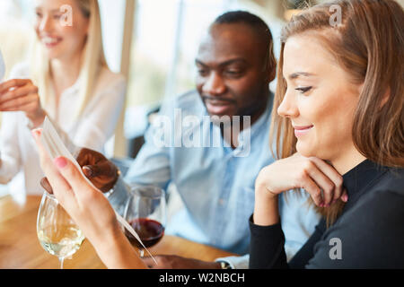 Young couple looks at the menu in the restaurant or bistro when ordering - Stock Image