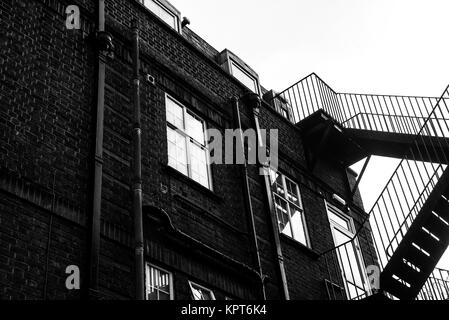 Black and white image of an external metal staircase used for emergency exits from a building - Stock Image