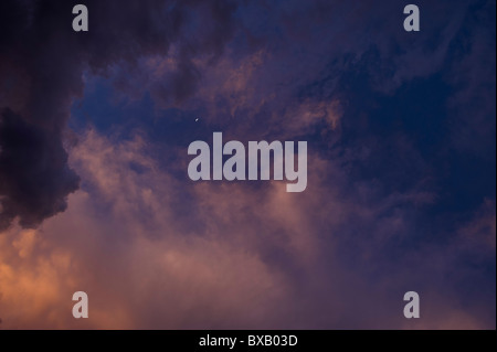 Stormy evening sky with crescent moon - Stock Image