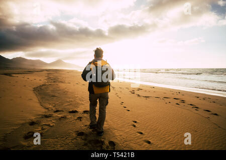 People in back view walking alone with his backpack on the desolation beautiful wild beach for alternative concept of tourism vacation - adventure and - Stock Image
