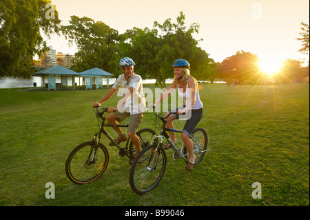 Couple riding bikes in the park - Stock Image