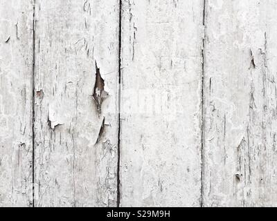 A textured wood background image of wooden boards with cracked and blistering white paint - Stock Image