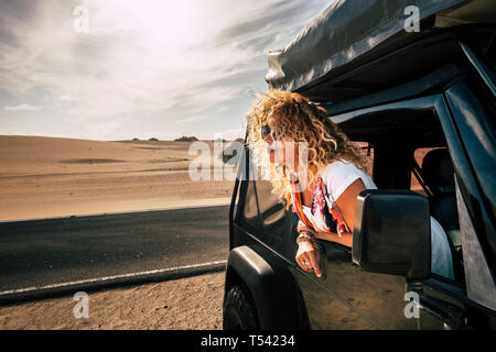 Beautiful lady caucasian people female enjoy th ewind in the outdoor nature out of her black car - desert outdoor around and alternative vacation jour - Stock Image