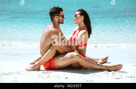 Romantic style portrait of a young couple relaxing on a beach - Stock Image