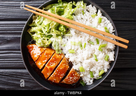 Japanese chicken teriyaki with rice and fresh salad close-up on a plate on the table. horizontal top view from above - Stock Image