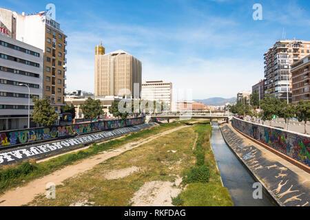 Malaga Spain. Guadalmedina river of Malaga City with former post office Correos Building left, Málaga, Spain. - Stock Image