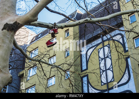 Kreuzberg-Berlin. Trainers hanging in tree outside Housing developemt, modern apartment building in Gitschiner Str. - Stock Image
