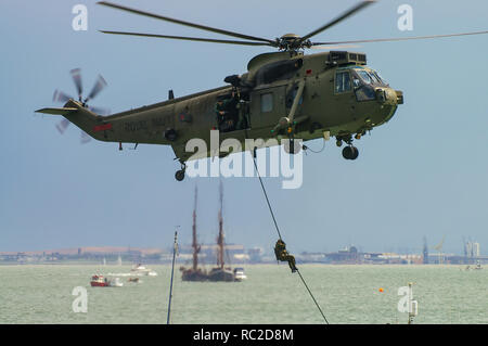 British Royal Navy Commando Sea King helicopter with Royal Marines fast roping down to a boat in a hostage rescue practice operation scenario - Stock Image