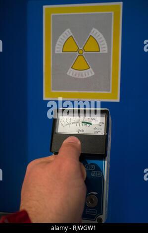 Hand-held radiation survey instrument detecting moderate radiation. Ionizing radiation hazard symbol as background - Stock Image